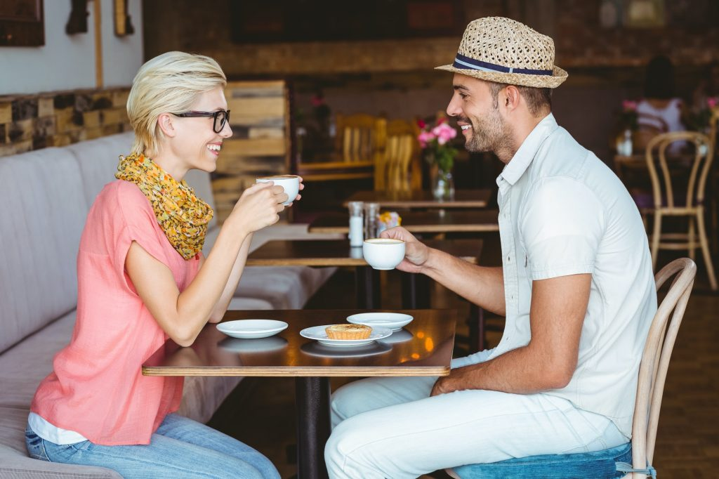 Cute couple on a date talking over a cup of coffee at the cafe