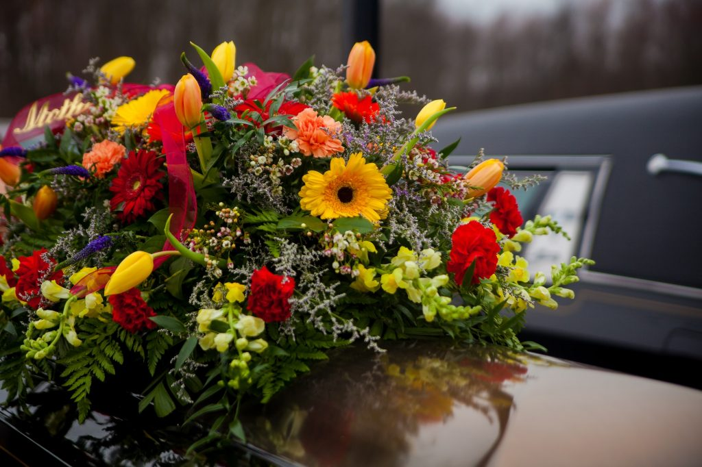 Carers - Funeral Casket and flowers next to hearse
